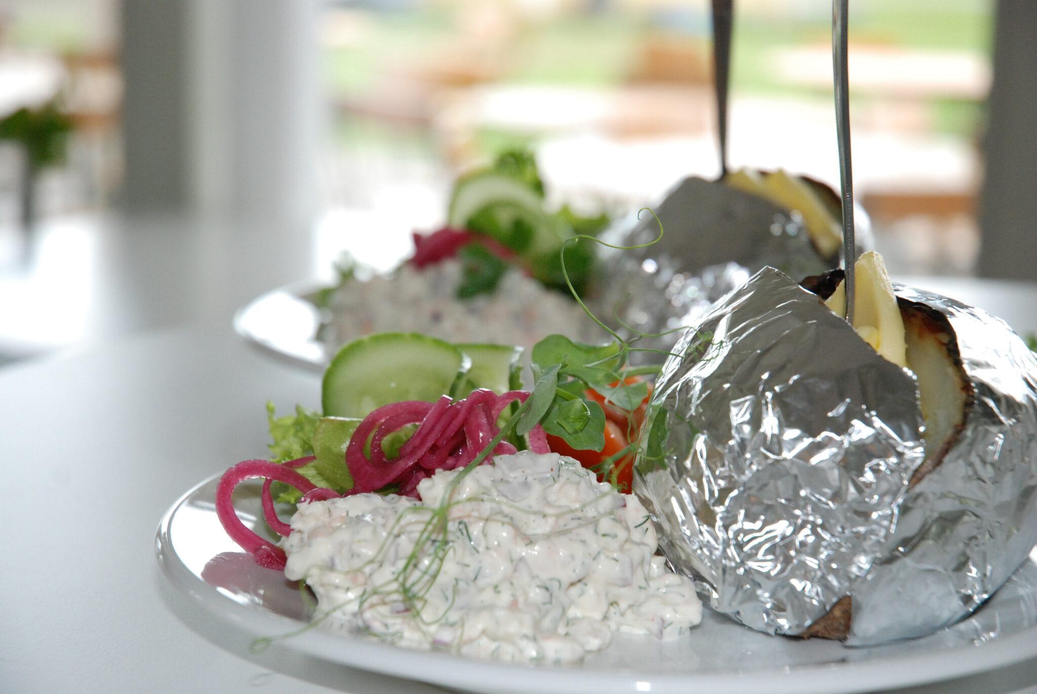Bakad potatis, serveras med sallad, välj mellan vår egen kycklingröra eller skagenröra